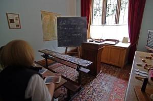 Im Lernzimmer von Lanhydrock kann man sich selbst auf alte Schulbänke setzen, mit der Schiefertafel etwas schreiben und die diversen Unterrichtsmaterialien im Schrank auf der rechten Seite anfassen.